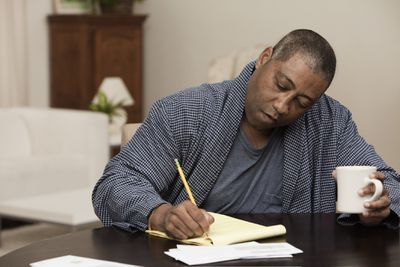 man holding coffee makes a budget list on a notepad