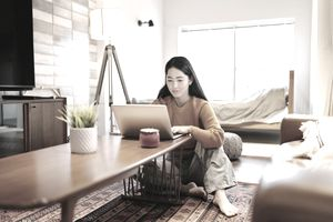 Young Woman Seated at Coffee Table Using a Laptop in an Apartment
