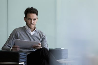 Seated man looking over report