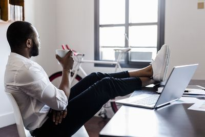 Businessman relaxing in home office with feet on desk