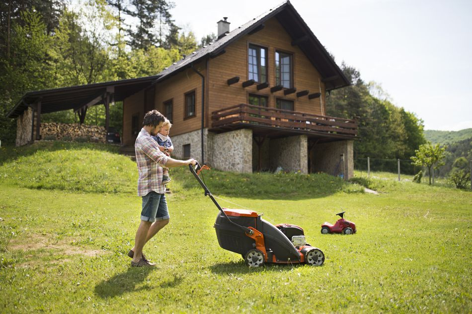 Father carrying his little son as he mows the lawn in front of a chalet-type home