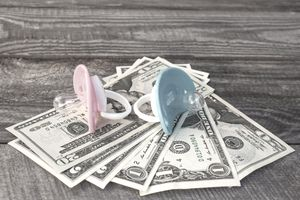 Blue and pink pacifiers on the background of money.