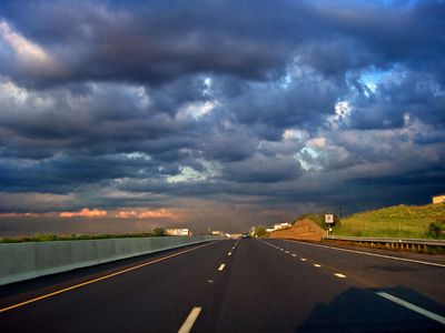 Shadow of a car on a highway with storm clouds threatening bad driving conditions