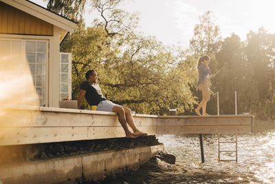 A man lounges on a deck above a lake while a woman stands nearby
