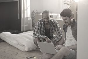 Two men moving into a new home, Looking at laptop