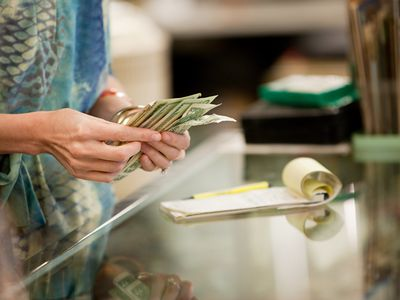 a woman counting money at a counter