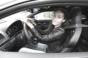 Young woman sitting in the driver's seat of a car.