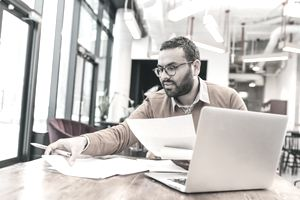 Small business owner doing paperwork in front of laptop