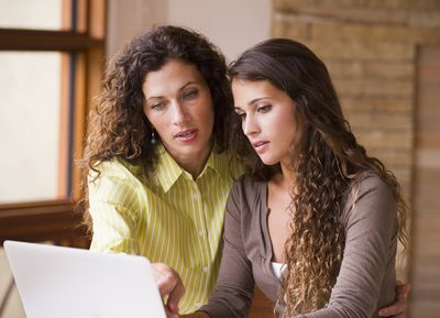 two women with long brown curly hair looking at a document on a computer