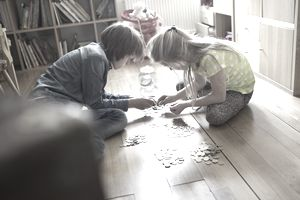 Two children counting coins together on the floor.