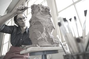 Woman using sculpting tools on a sculpture as she thinks about turning it into a business