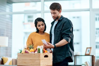 Young couple scrutinizing grocery receipt at home