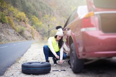 Woman fixing a car tire on the side of the road