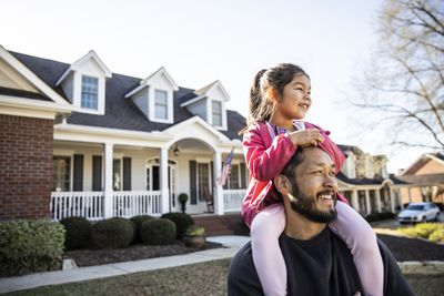 Girl sits on her dad's shoulders in front of house