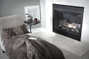A divan with a fuzzy blanket and a book in front of a burning fireplace