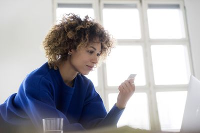 A woman looks at her credit card and her computer as she contemplates adding credit insurance to her card