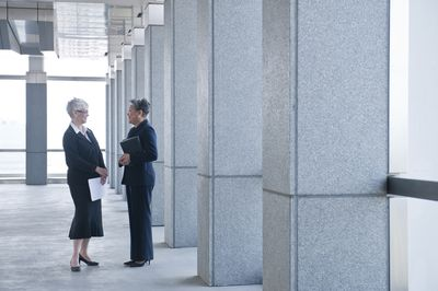 Two federal employees nearing retirement age talking in the hallway of a federal building.