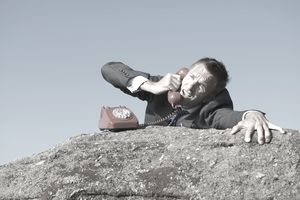 Desperate Businessman on the Phone Call from Rock Cliff
