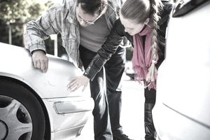 Man and woman looking at car after accident to see if car insurance will cover their damaged car