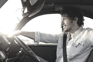 A smiling man grips the steering wheel of a car with one hand.