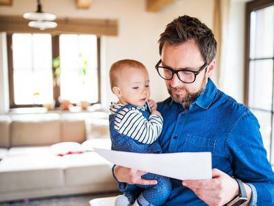 Man holds a baby in one arm while reviewing insurance paperwork