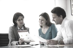 an accountant talks to a couple about a financial plan as she shows them a brochure of information