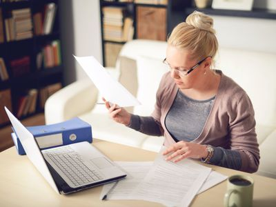 Blonde woman shuffling through papers working from home