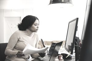 Focused female IT professional holding document while looking at computer in creative office