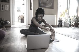 A woman does an at-home workout through a paid streaming service her credit card discounts.