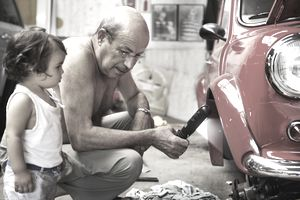 Man working on a classic car in his driveway while a small girl watches.