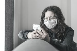Young woman covering her face with surgical mask and using smartphone to find information about coronavirus spread on internet