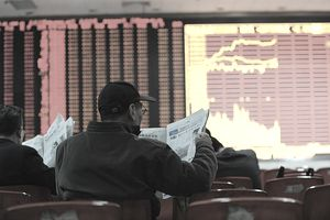 Man reading newspaper at stock exchange, representing short selling stock.
