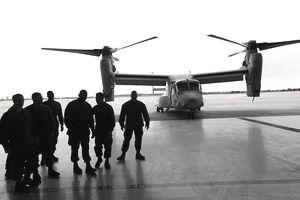 Marines from the 3rd Marine Aircraft wing walk by a V-22 Osprey