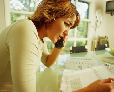 Concerned-looking woman on phone while holding a bill