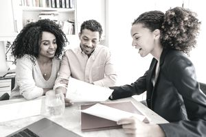 couple speaking with financial advisor at desk
