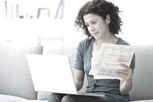 Woman working on a laptop while holding some financial statements