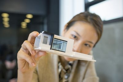 A woman holds up a model of a sleek home and looks closely at it.