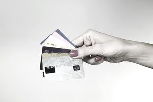 A person hold several reward credit cards spread out like a fan in their hand