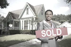Woman holding sold sign in front of her home.