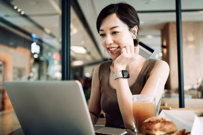 Beautiful smiling young Asian woman having meal in a cafe, shopping online with laptop and making mobile payment with credit card on hand