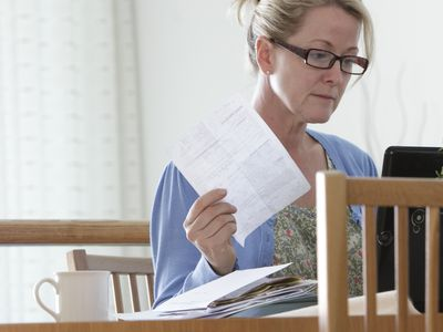 a woman working on a laptop holding a bill