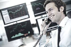 A young investor smiles while talking into his telephone, behind him computer monitors display charts and graphs.