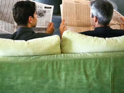 Two men on green couch reading newspaper financial tables