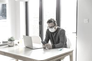 Man working from home. Using smartphone