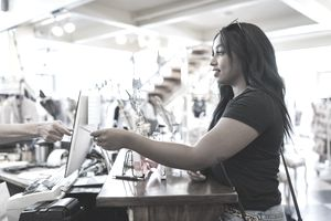 Young woman paying cashier in clothing shop