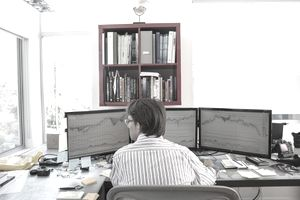 a trader sitting in front of three side-by-side computer monitors