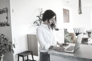 person in white shirt standing at countertop using laptop