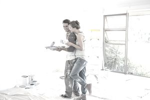 A young couple in paint splattered work clothes take a break from painting the interior of a house to share a playful hug.