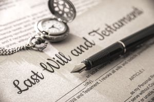 Fountain pen and a pocket watch sitting atop a last will and testament