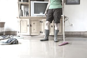 A woman stands in her living room in shorts and rubber boots, pausing while mopping up flood water from the floor with a mop and wet towels.